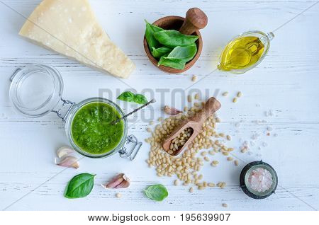 Pesto genovese - traditional Italian green basil sauce with raw ingredients on white wooden background. Basil leaves in mortar Parmesan cheese pine nuts olive oil garlic and salt. Top view.