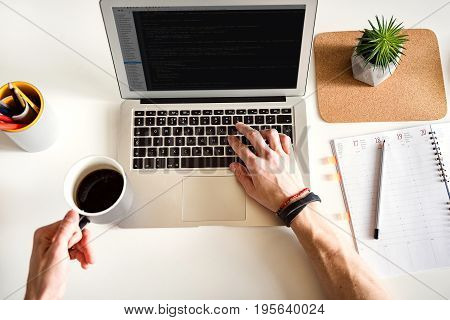 Top view close up man arms typing on keyboard of laptop. Employee drinking cup of hot coffee during work in office