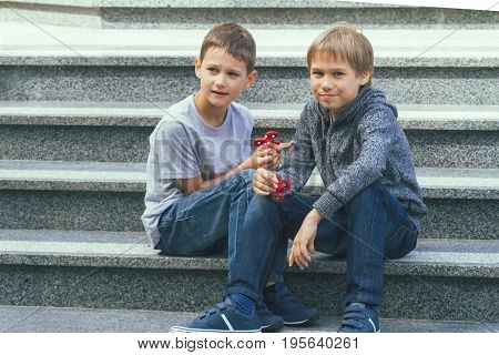 Two boys playing with spinners outdoors sitting on the stairs