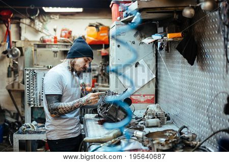Side view portrait of modern tattooed man fixing broken  parts at table in  workshop
