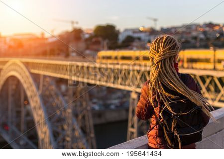 Young woman with dreadlocks (from the back) meets sunset on the viewing platform opposite the Dom Luis I bridge across the Douro river in Porto, Portugal.