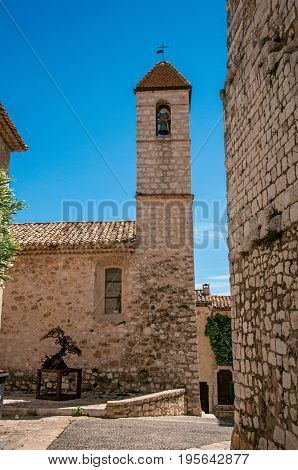 View of alley and church with stone steeple tower in Saint-Paul-de-Vence, a lovely well preserved medieval hamlet near Nice. Located in Alpes-Maritimes department, Provence region, southeastern France