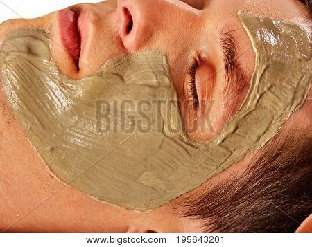 Mud facial mask of man in spa salon. Massage with clay full face. Close up man lying on spa bed on therapeutic procedure . Cropped shot of home cosmetics with egg yolk.