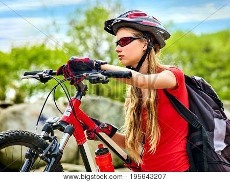 Woman on bicycle ride mountain. Girl traveling in summer park. Early morning with blue sky and clouds. Cycling person with rucksack in special park. Sport trip is good for health.