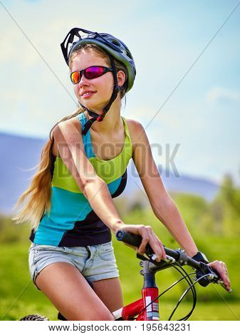 Woman traveling bicycle in summer park. Womens road bike for running on green grass aganist blue sky with white clouds. Female in school trip. Correct mental development of teenager idea.