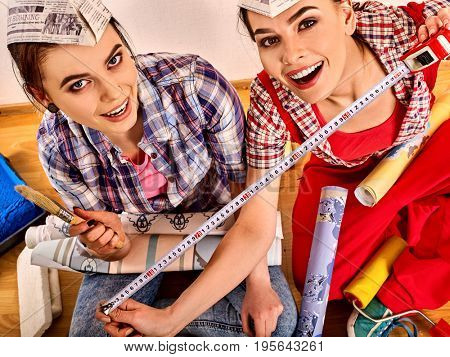 Repair home women holding construction measuring tape wallpaper. Girls renovation apartment . Top view workers sit on floor and rest from work done. Sisters paint walls.