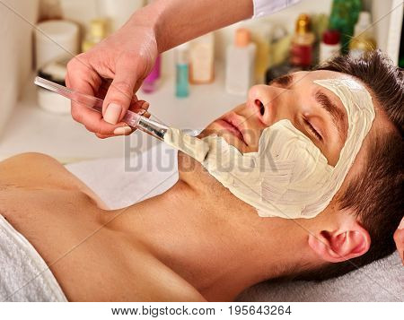 Mud facial mask of man in spa salon. Healing massage with clay full face. Male lying spa bed. Beautician with cosmetic brush therapeutic procedure us anti-aging cosmetic .