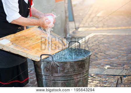 Elderly Woman Washes The Laundry With Bucket And Wooden Board As She Once Did
