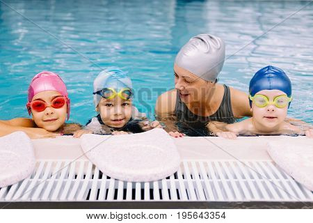 Cute kids having a swimming lesson on indoor swimming pool toned image