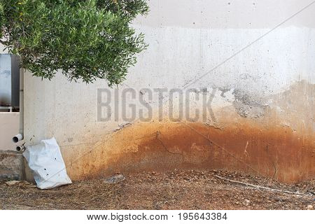 abandoned grunge cracked stucco wall, sandy dirty ground