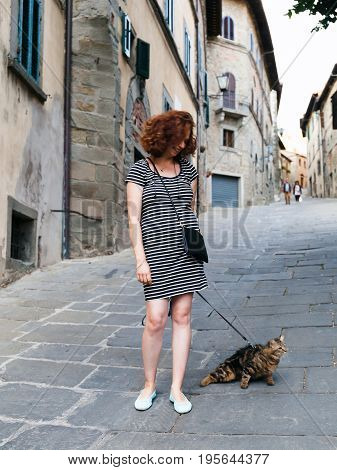 Cortona Italy - July 15 2017: Girl strolls through the streets of the small Tuscan town carrying her cat on the leash.