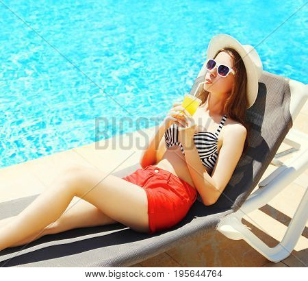 Summer Holidays - Pretty Young Woman Drinks Juice From Cup On A Deckchair Over A Blue Water Pool Bac