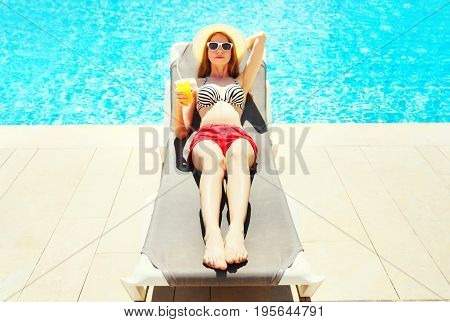 Summer Holidays - Pretty Woman Resting With Juice From Cup On A Deckchair Over A Blue Water Pool Bac