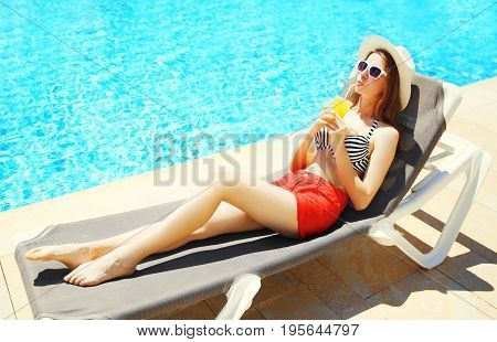 Summer Holidays - Pretty Woman Drinks Juice From Cup On A Deckchair Over A Blue Water Pool Backgroun