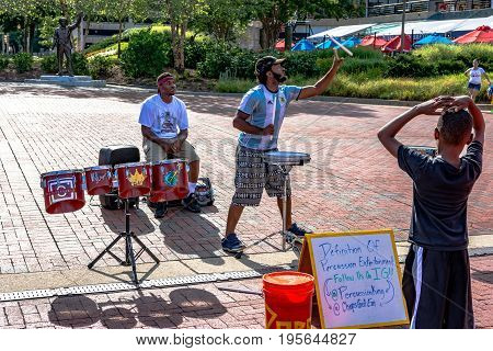 Baltimore Maryland USA - July 8 2017: Percussion street performers putting on a show for passersby at the Inner Harbor in Baltimore Maryland.