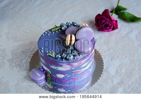 Unique beautiful dark cake with berries and macaroons with rose on white background