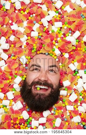 Face of bearded guy looking out of sweets trying to crack candy drop with teeth.