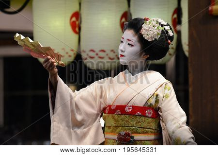 KYOTO, JAPAN - MARCH 20, 2016 - A young geisha entertains onlookers with a dance and fan performance in Kyoto