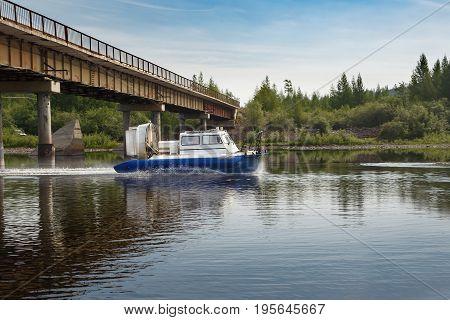 An air-cushion boat passes a bridge on a river