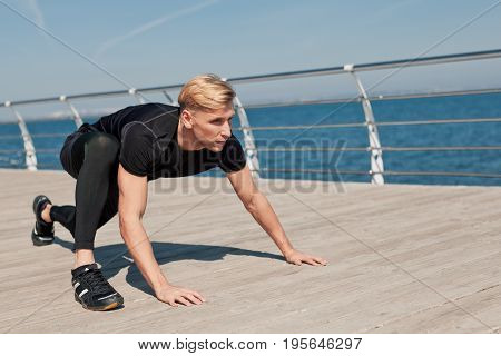 Side view of fit man preparing to start a run standing on pier at seaside.