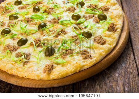 Italian seafood pizza with tuna closeup on wood background, one slice cut off, top view
