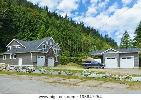 Brand new family house with car and boat parked on gravel driveway. New residential house and detached double garage on country side in British Columbia Canada