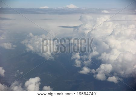 the top of the mountain is visible through Cumulus clouds, with altitude of the aircraft, a powerful mountain range, the background haze of clouds, above a certain level the blue sky