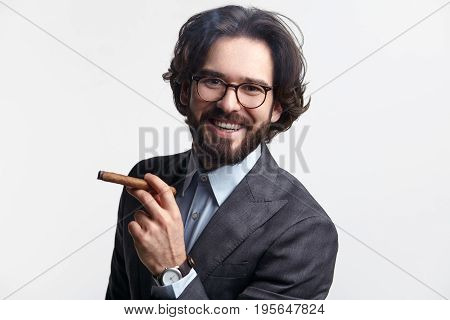 Portrait of successful man in glasses and suit holding cigar and looking at camera on white.