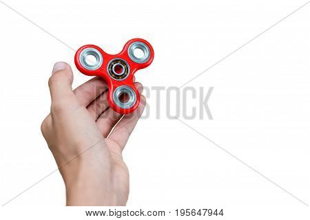 Fidget spinner. Red hand spinner, fidgeting hand toy rotating on child's hand. Stress relief. Anti stress and relaxation adhd attention fad boy concept. Free space for text