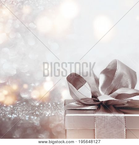 Gift with a loop on abstract silver glitter bokeh background for a surprise