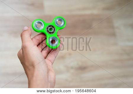 Fidget spinner. Green hand spinner, fidgeting hand toy rotating on child's hand. Stress relief. Anti stress and relaxation adhd attention fad boy concept. Free space for text