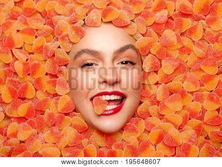 From above shot of woman lying in fruit jelly looking at camera.