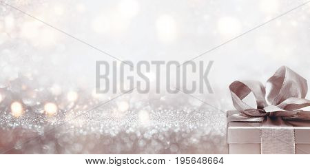 Gift on abstract silver glitter bokeh background for a festive concept