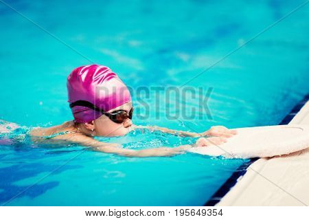 Little girl in swimming training on indoor swimming pool toned image