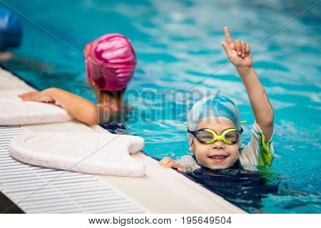 Kid who won the swimming race on indoor swimming pool toned image