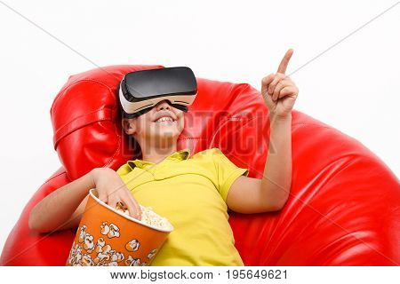 Smiling young boy sitting in beanbag wearing virtual reality goggles and having a popcorn from a basket.