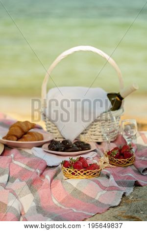 Summer time at the sea. Romantic picnic on the beach - wine strawberries and sweets. Selective focus.