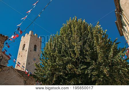 View of stone steeple tower next to church and tree in Vence, a stunning medieval hamlet completely preserved. Located in the Alpes-Maritimes department, Provence region, southeastern France