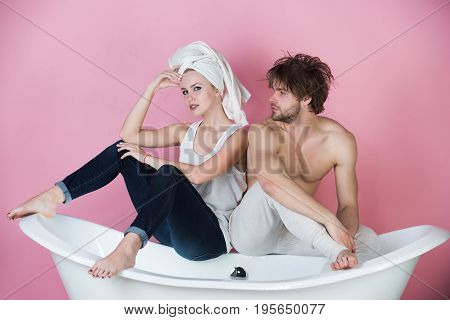 man and woman. couple in love with towel sitting on white bathtub on pink background family relationship and romance spa and beauty relax and hygiene healthcare