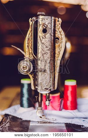 Old sewing machine, Classic retro style manual sewing machine ready for sewing work. The machine is old style made of metal with floral patterns