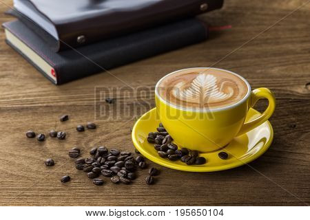Latte coffee or cappuccino coffee in yellow cup with latte art decorated by coffee beans and notebooks on wooden table