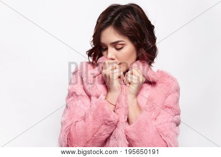 Horizontal studio shot of pretty sensual woman with eyes closed in pink jacket.