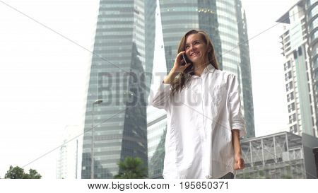 Businesswomanin white shirt answer phone, receive good news, excited happy cheerful.