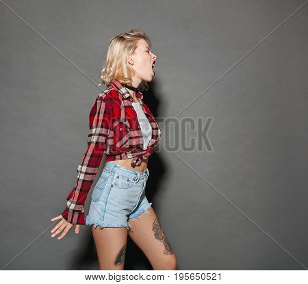Side view of trendy tattooed girl shouting and expressing anger on dark background