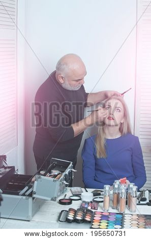 Visagiste applying eye makeup on girl face with brushes. Woman pretty fashionable model with long blond hair in blue dress sitting at table with cosmetic kit in beauty salon. Visage make up