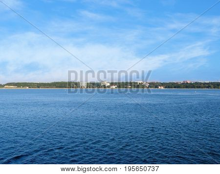 View of the shore of Estonia from the Gulf of Finland. Calm sea and blue sky