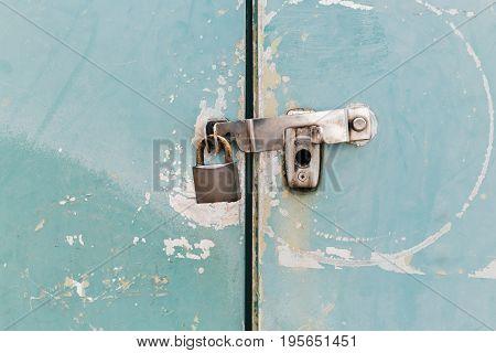 Key lock locked on vintage metal fence. Security Concept.