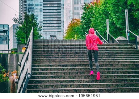 Runner running up the stairs on rain run in Vancouver city. Staircase cardio workout jogger training.