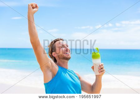 Success fitness man runner drinking protein shake muscle gain or weight loss goal winning. Running athlete on beach with healthy bottle drink