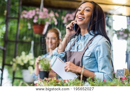 Smiling Young African American Florist Holding Notebook And Talking On Smartphone While Colleague Wo